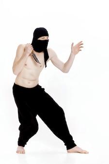 L'uomo ninja tiene il coltello ed è pronto ad attaccare su sfondo bianco