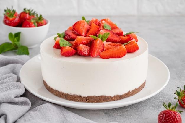 Nessuna cheesecake al forno con fragole fresche e menta sopra su un piatto bianco white
