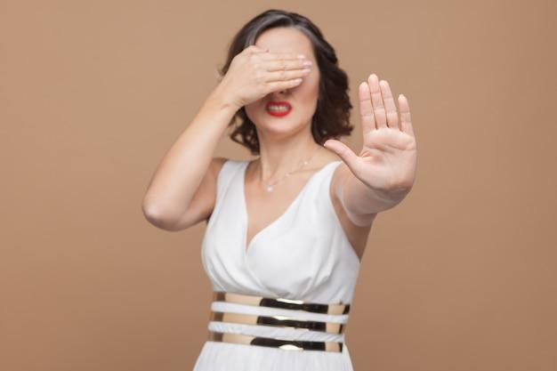 No, divieto! la donna di mezza età non ha bisogno di vederlo. donna espressiva emotiva in abito bianco, labbra rosse e acconciatura riccia scura. studio shot, indoor, isolato su sfondo beige o marrone chiaro
