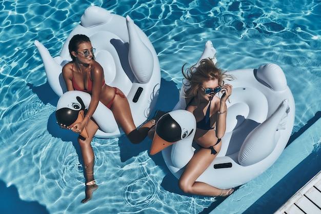 Non c'è modo migliore per trascorrere l'estate. vista dall'alto di due belle giovani donne in bikini che guardano lontano e sorridono mentre galleggiano su grandi cigni gonfiabili