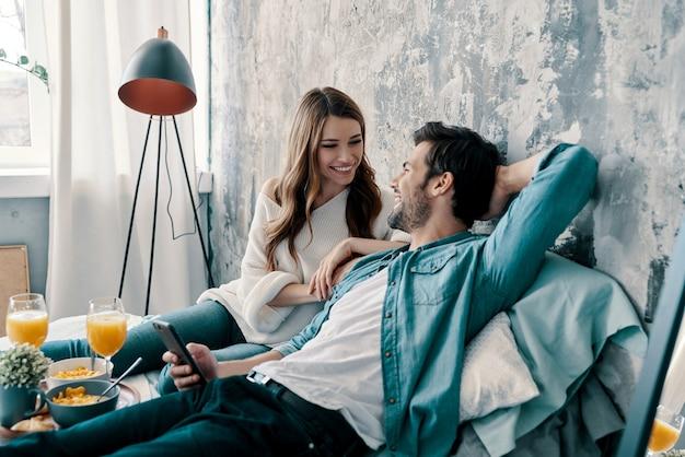 Nessuna preoccupazione. bella giovane coppia che fa colazione mentre trascorre il tempo a letto a casa
