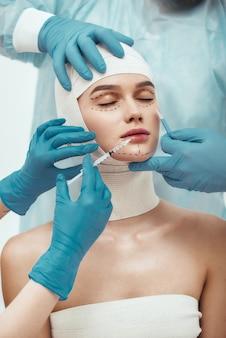 Nessuna possibilità di rughe giovane donna con la testa fasciata che tiene gli occhi chiusi mentre è in plastica