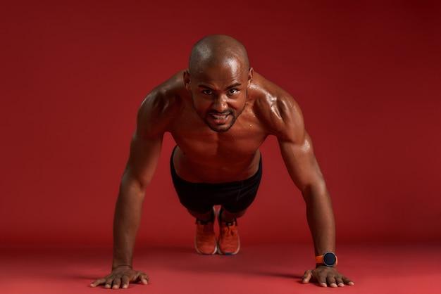 Nessun limite per tutta la lunghezza del forte uomo africano in abbigliamento sportivo che fa flessioni isolate sopra