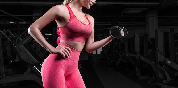 Nessun nome ritratto di una ragazza in tuta in posa in palestra con manubri. concetto di fitness.