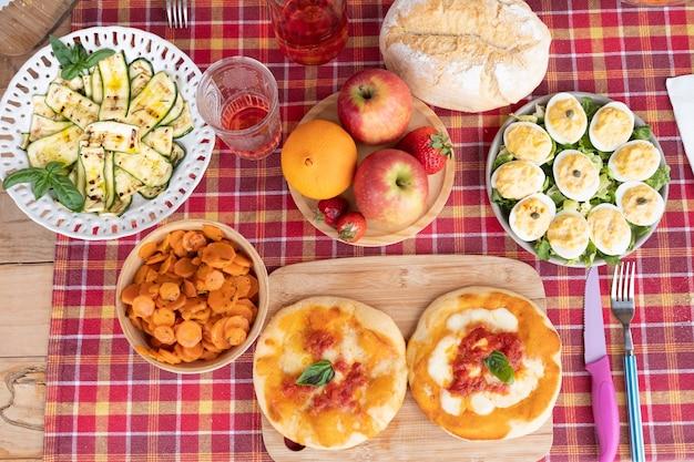 Nessuna gente ma il tavolo è pronto per il pranzo. tovaglia a quadretti rossa su un pannello di legno. uova, pizza e verdure su piatto o tagliere. bicchiere da vino rosso