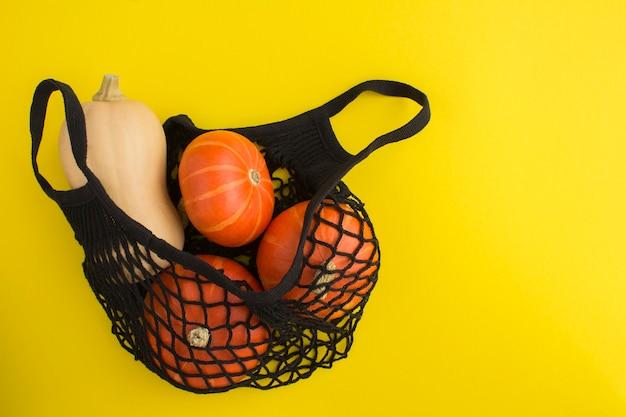 Nessun concetto di sacchetto di plastica. shopping bag in rete nera con zucca su sfondo giallo.