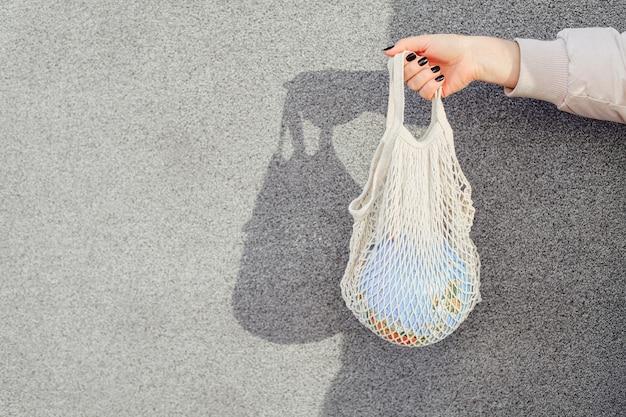 Nessun concetto di plastica. mani che tengono il pianeta terra globus in borsa a rete.