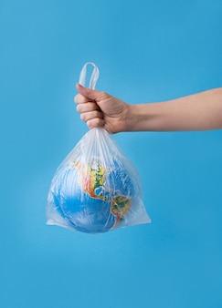 Nessun concetto di plastica. mani che tengono il pianeta terra in un sacchetto di plastica.