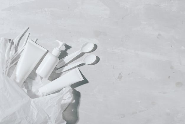 Nessun concetto di riciclo di plastica bianco piatti di plastica piatti tazze cucchiaio su sfondo di pietra. copia spazio. vista dall'alto