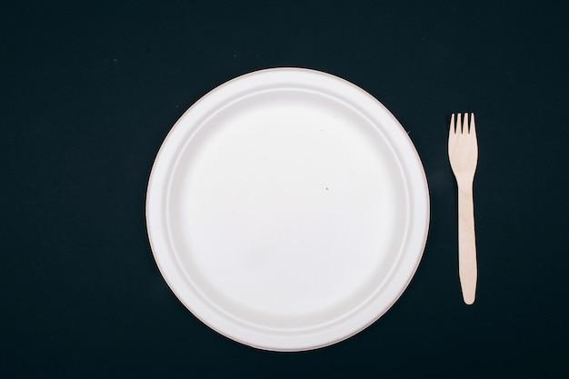 No alla plastica. piatto e forcella di carta di legno ed ecologici su fondo scuro, vista superiore. tempo di cambiare. nuove regole per ridurre i rifiuti di plastica, direttiva ue. divieto di plastica monouso.