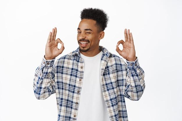 Nessun problema. il ragazzo afroamericano sorridente fiducioso assicura tutto sotto controllo, strizzando l'occhio e mostrando il gesto ok ok, approva smth buono, lode, essendo assertivo nella sua scelta su bianco.