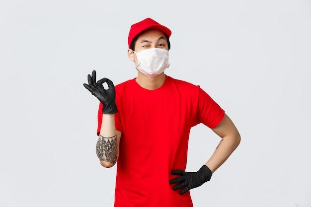 Nessun problema, consegna il tuo pacco. il ragazzo di consegna asiatico allegro in uniforme rossa, mostra il segno giusto e fa l'occhiolino, assicura la sicurezza del pacchetto. indossare guanti protettivi e mascherina medica, stare al sicuro e fare acquisti online