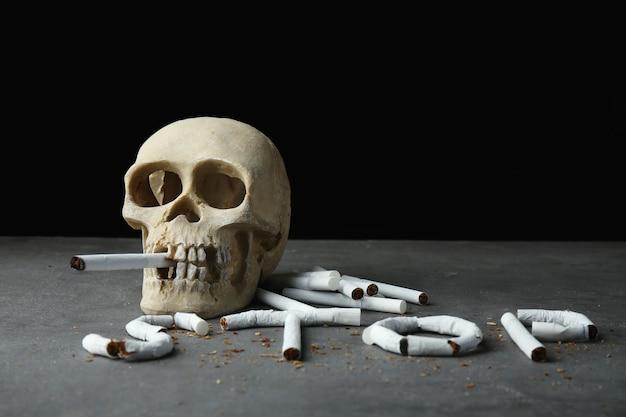 Nessun concetto di fumare. parola stop fatta di sigarette e teschio su sfondo grigio