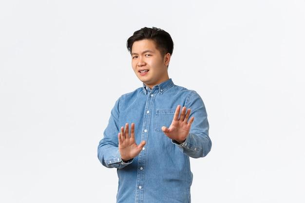 No grazie. uomo asiatico non divertito e infastidito allontanarsi dai guai, alzando le mani nel gesto di arresto