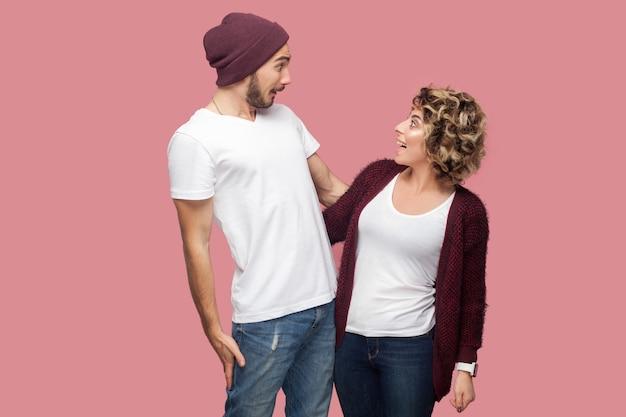 Non c'è modo. ritratto di coppia eccitata di amici in stile casual in piedi e guardandosi l'un l'altro con facce incredibili, grandi occhi e sorriso a trentadue denti. isolato, interno, girato in studio, sfondo rosa