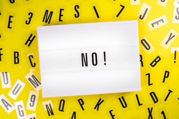 Nessuna parola sul lightbox su sfondo di lettere sparse di alfabeto di plastica