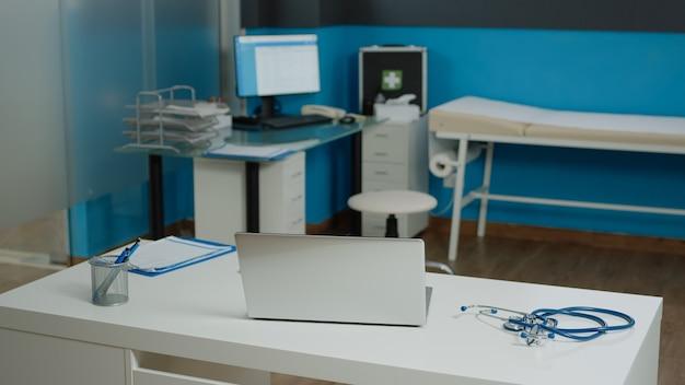 Nessuno nello spazio di consultazione presso la clinica sanitaria utilizzato per l'esame e l'incontro con i pazienti. ufficio medico vuoto con attrezzature e strumenti medici, stetoscopio e dispositivi tecnologici