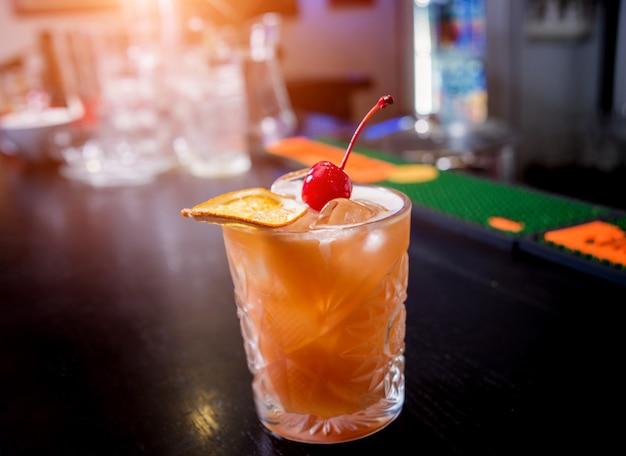 Cocktail analcolico con limone e arance al bancone bar in legno. ristorante.