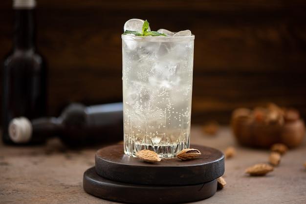 Birra allo zenzero analcolica con ghiaccio in bicchieri alti su un tavolo di legno