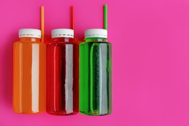 Bevande gassate multicolori analcoliche con tubi di cocktail in bottiglie di plastica su sfondo rosa