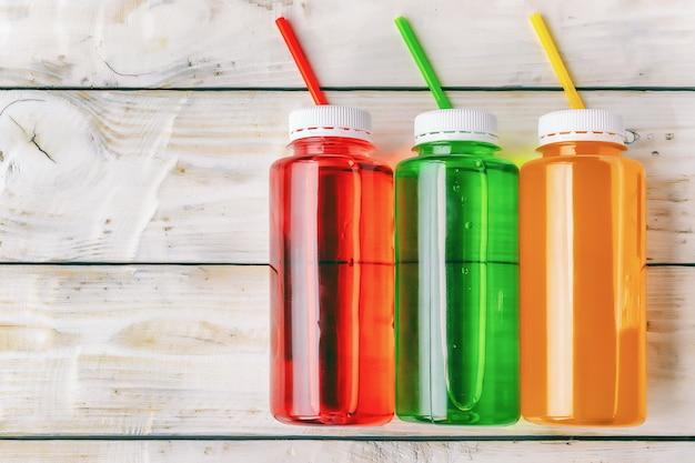 Bevande gassate multicolori analcoliche con tubi di cocktail in bottiglie di plastica su fondo in legno, concetto di bevande su base naturale, isotonica fitness