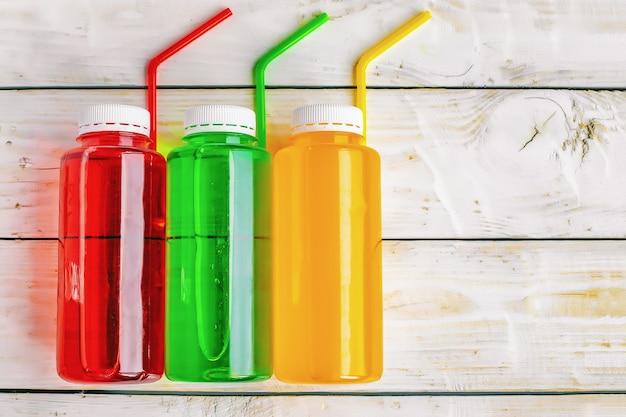 Bevande gassate multicolori analcoliche con tubi di cocktail in bottiglie di plastica su fondo in legno