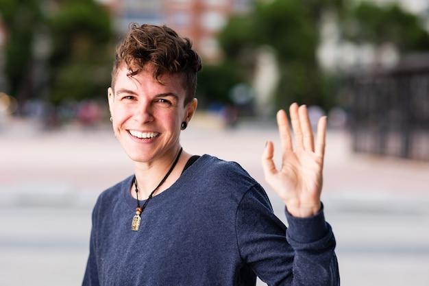 Maschiaccio transgender non binario che guarda il saluto della telecamera e agita la mano sorridendo durante internet