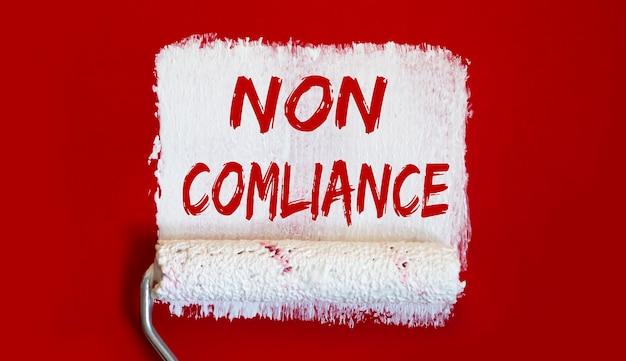 Non conformità. un barattolo aperto di vernice con pennello bianco su sfondo rosso.