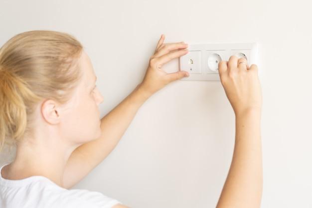 Lavoro non femminile. riparazione e decorazione. la donna ripara gli sbocchi in un nuovo appartamento