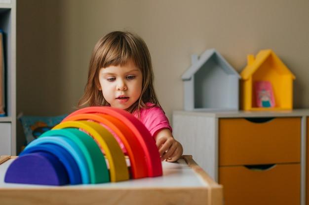 Concetto di giocattoli in legno non di plastica. bella bambina che gioca con il giocattolo di legno colorato arcobaleno nella stanza dei bambini