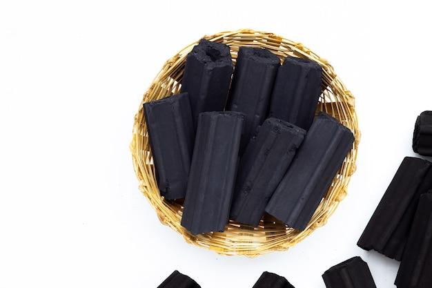 Carbone di legno non fumo in cesto di bambù su sfondo bianco.