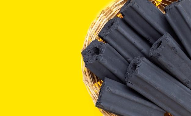 Carbone di legno non fumo in cesto di bambù su sfondo giallo.