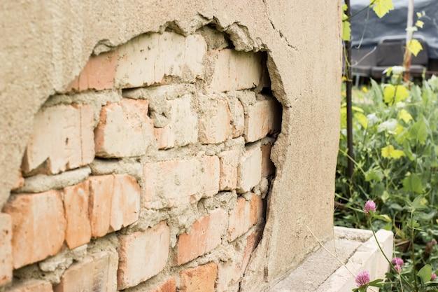 Intonaco non tecnologico. costruzione parete di facciata in gesso incrinato con mattoni.