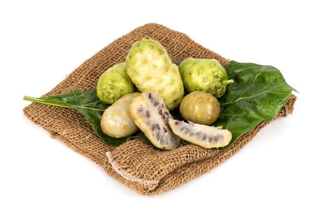 Frutti di noni e foglia verde isolati su superficie bianca.