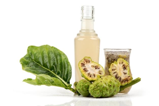 Noni frutti, foglie verdi e succhi di frutta isolati.