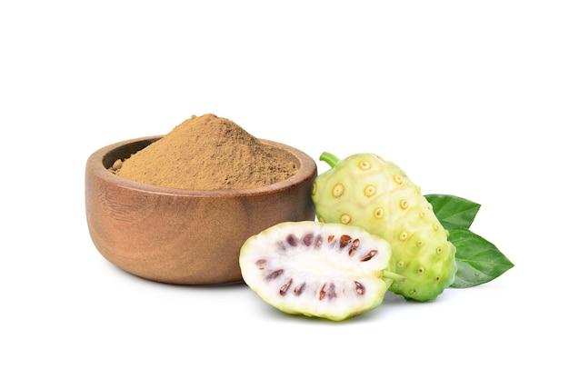 Noni o morinda citrifolia in polvere nella ciotola di legno con frutti e foglie isolati su sfondo bianco.