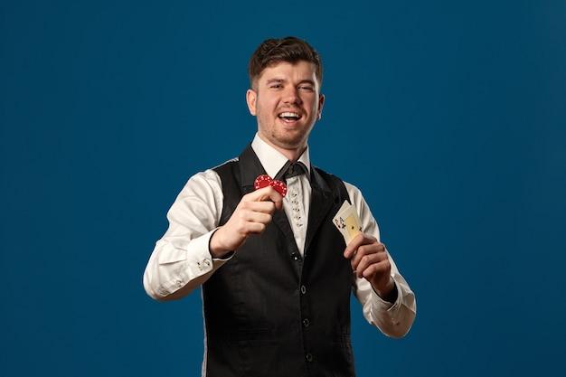 Noob a poker in canottiera nera e camicia bianca con due fiche rosse e assi in posa su sfondo blu...
