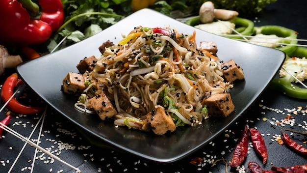 Tofu fritto di noodle e insalata di verdure su un piatto. cibo della cucina cinese.