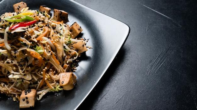 Tofu fritto di noodle e insalata di verdure su un piatto. cibo della cucina orientale. pasto tradizionale