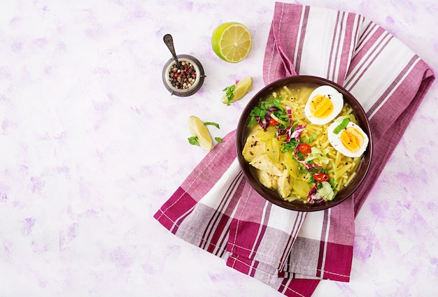 Minestra di pasta con pollo, sedano e uovo in una ciotola su un tavolo luminoso.