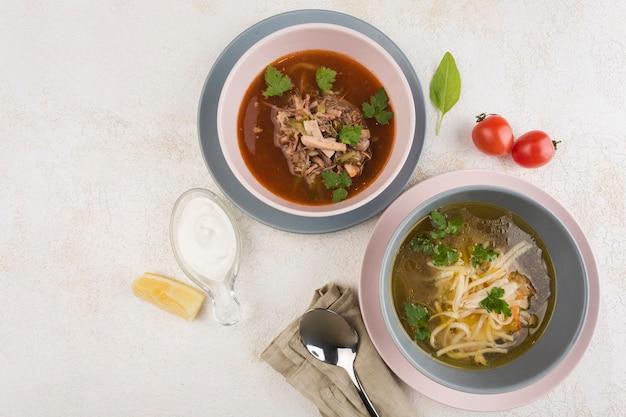 Zuppa di noodle con pollo e solyanka con carne con salsa bianca su piatti con tovagliolo su sfondo chiaro. vista dall'alto con uno spazio di copia per il testo. cibo dal ristorante.