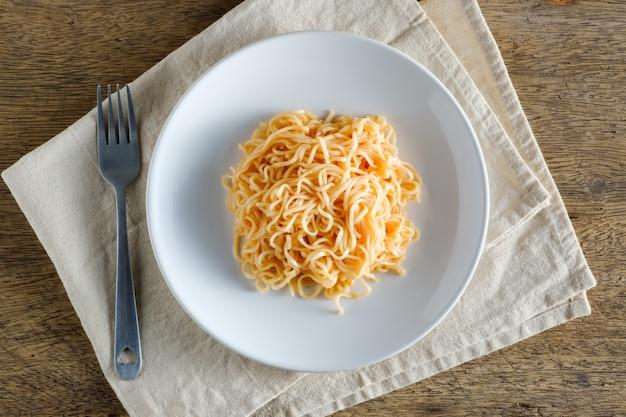 I noodles sono in un piatto bianco rotondo posizionato su una napery