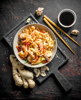 Tagliatelle in un piatto su un tagliere con zenzero e salsa di soia sul tavolo rustico nero