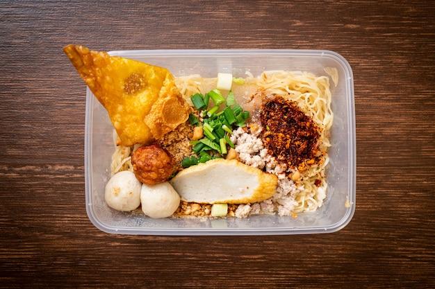 Tagliatelle con polpette di pesce e carne di maiale macinata nella scatola di consegna