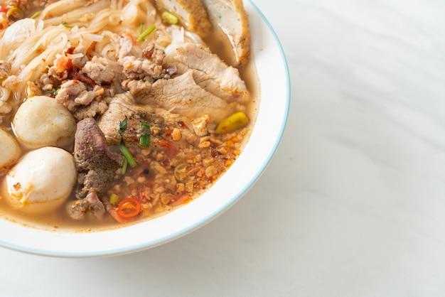 Noodles con maiale e polpette in zuppa piccante o noodles tom yum in stile asiatico