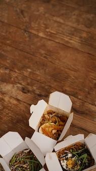 Tagliatelle con carne di maiale e verdure in scatola da asporto sul tavolo di legno. consegna di cibo asiatico. cibo in contenitori di carta su fondo di legno. foto verticale