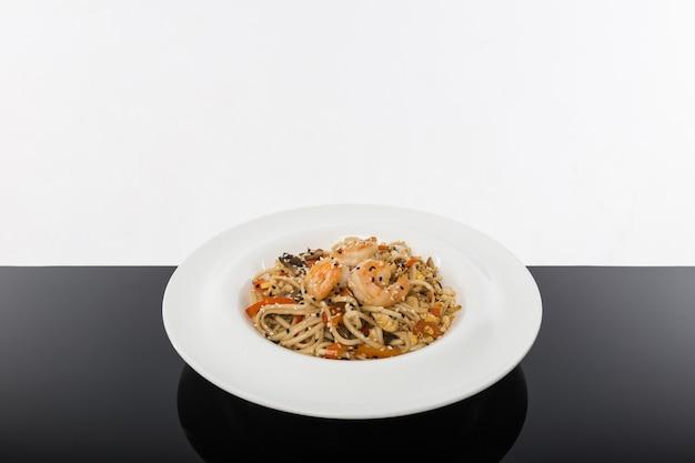 Tagliatelle ai frutti di mare su un tavolo nero con uno sfondo bianco