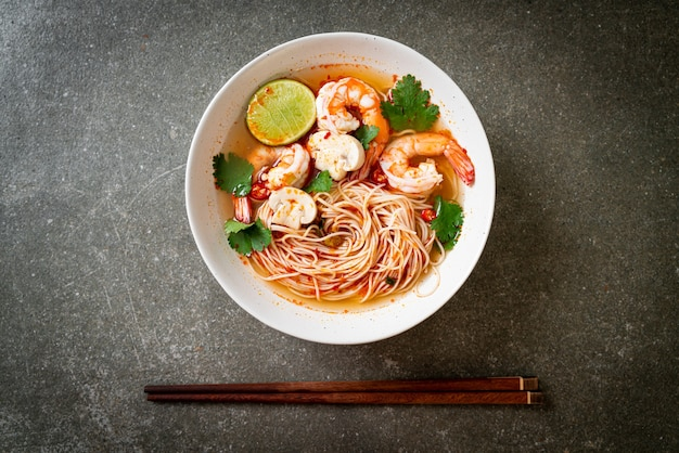 Noodles con zuppa piccante e gamberi in ciotola bianca (tom yum kung) - cucina asiatica