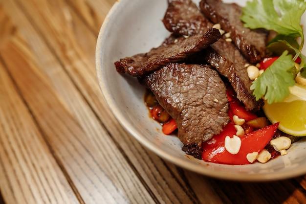 Tagliatelle con carne di vitello e verdure su un tavolo grigio.