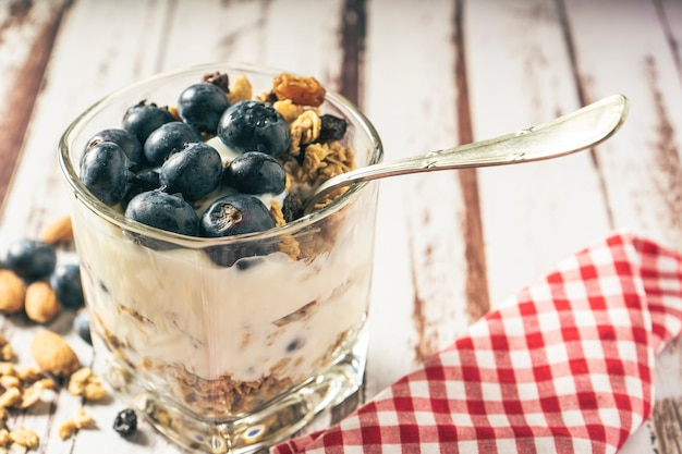 Vista normale di un bicchiere con un parfait di yogurt, mirtilli e muesli su un tavolo in legno rustico. concetto di alimentazione sana e naturale.